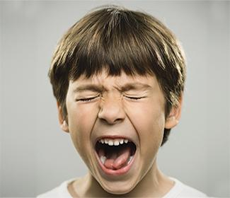 Upset boy with eyes closed and mouth open against a grey background.