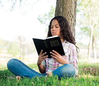 A girl sitting outside on a sunny day reading the bible in the grass.