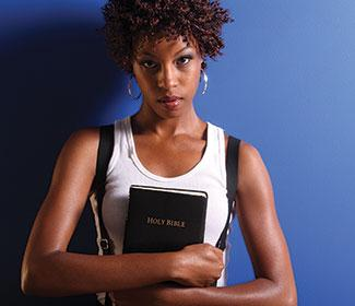 Woman holding bible standing in front of a blue wall.