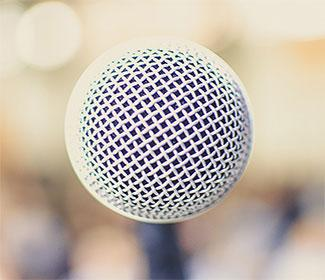 Close up of a microphone on a stage. The background is blurred.