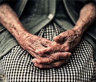 Close up of elderly hands folded on lap