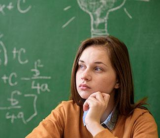 female student in front of chalkboard with math equations