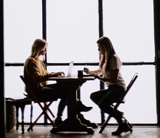 Two women sitting at a table and talking.