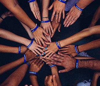 Birds eye view of hands together in a circle.