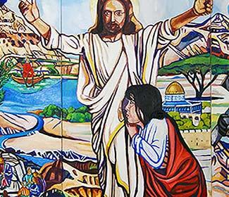 Colorful painting of Jesus with Mary on her knees holding his waist.