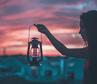 Woman holding a lantern with as the sun sets.