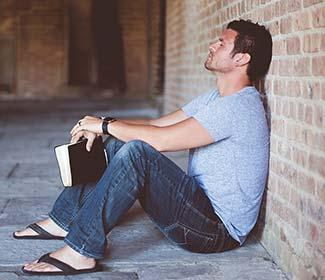 Man sitting on floor with his back against a brick wall holding a bible.