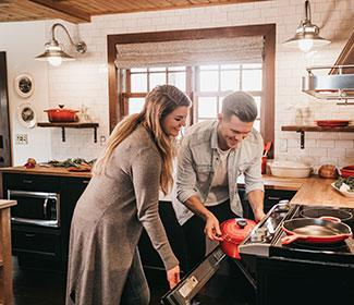 couple putting food in the stove