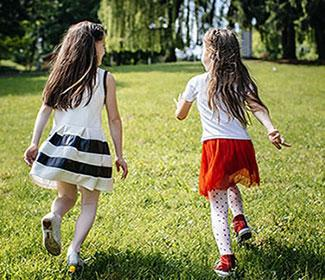 Two girls running on grass on a sunny day.