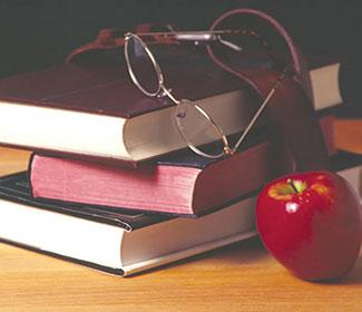 Stack of school books and an apple.