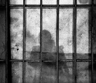 shadow figure behind prison bars
