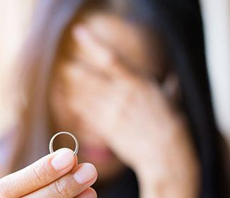 sad woman with hand over face holding a wedding ring