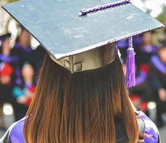 Woman with graduation cap facing an audience with her back to the camera.