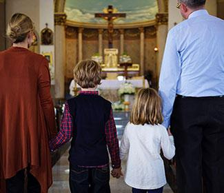 A mother, father, and their two children standing at a church alter.