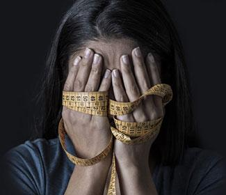 Woman with measuring tape around her hands as she holds them over her face.