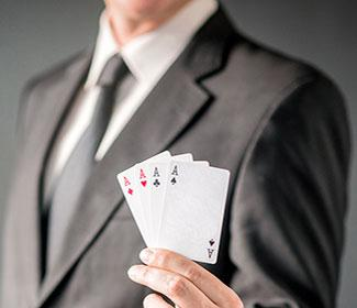 man in suit hold four ace playing cards