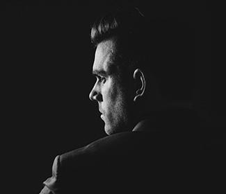 Grey scale image of man's profile with a black background.