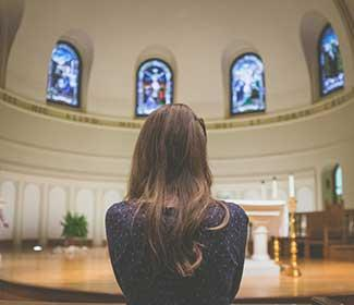 Woman with her back to camera praying at the front of a church.