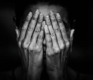 Grey scale image of woman with her hands covering her face.
