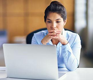 Woman sitting in front of a laptop.