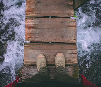Point of view image of feet on a wooden bridge with water rapids below.