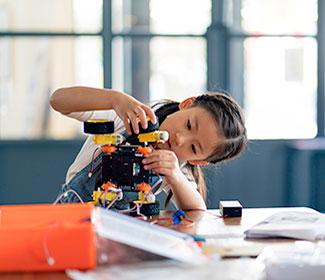 young girl building robot