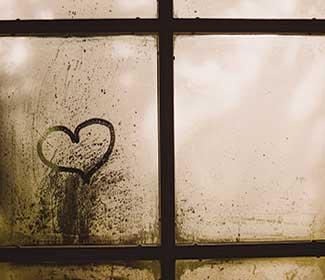 Foggy window pane with a heart drawn on it.