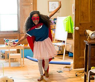 Young girl playing in her room with a superhero cape and mask on.
