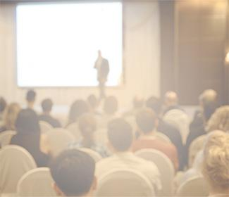 Out of focus image of man standing on a stage and talking to a crowd.