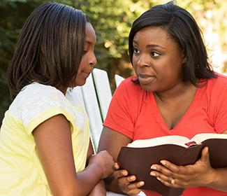 Woman reading bible to her daughter.