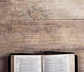 Birds eye view of an open bible on a wooden table