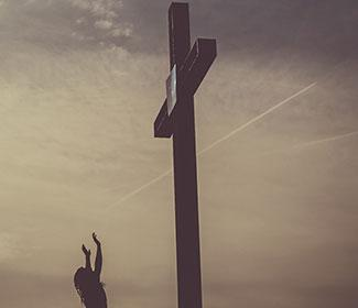 Person standing with arms in the air as they look up at a large cross.