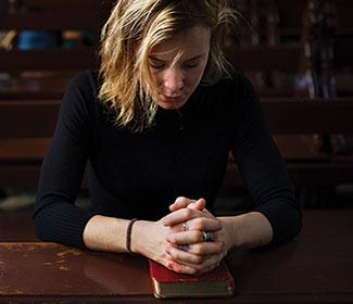 Woman sitting in empty church with hands folded in prayer.