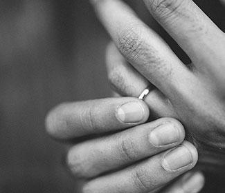 Grey scale image of mans hands with a wedding ring.