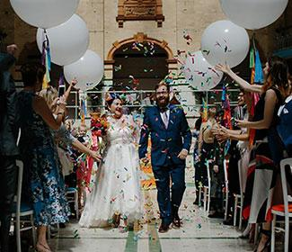 Husband and wife walking down the aisle after getting married, crowd throwing confetti.