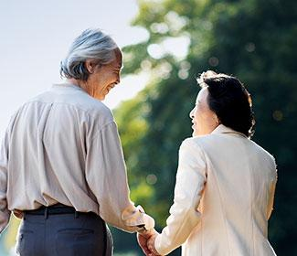 An older couple holding hands as they walk outside on a sunny day