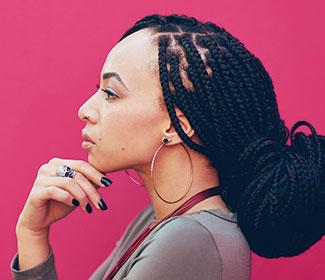 African American woman's profile as she stands in front of a pink wall