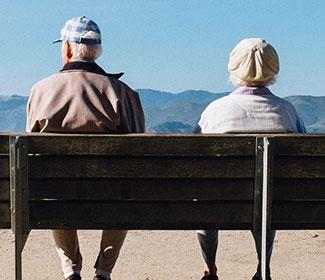 The back of an older couple sitting on a bench that overlooks mountains.