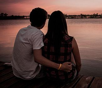 Couple sitting in front of a lake at sunset.