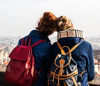 The back of two women as they lean on each other and gaze at a city view