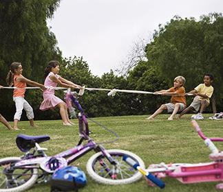 A group of kids playing a boy vs. girl game of tug of war in the grass