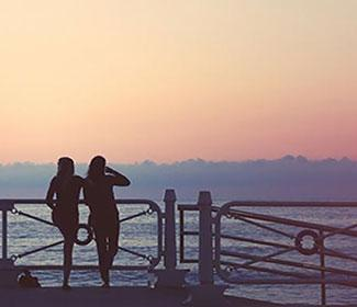 The back of two women standing on a dock of a bay at sunset