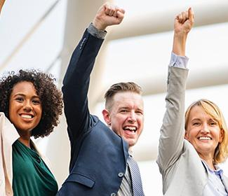 A group of diverse business people smiling with there fists in the air in celebration