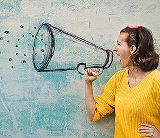 Woman with mouth open as she stands in front of an illustration of a megaphone.