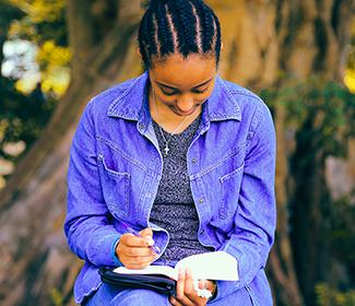 Black woman studying the bible outside