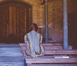 woman sitting alone in church: Silence—A Response to Abuse in the Church
