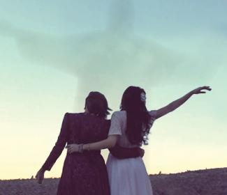 Two woman standing together with their arms outs, a silhouette of Jesus is seen in the sky.