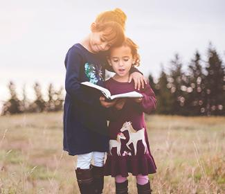Two young girls standing outside looking at a book.