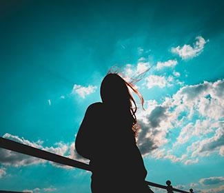 silhouette of girl standing with sky and clouds in the background