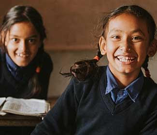female students smiling at their desks